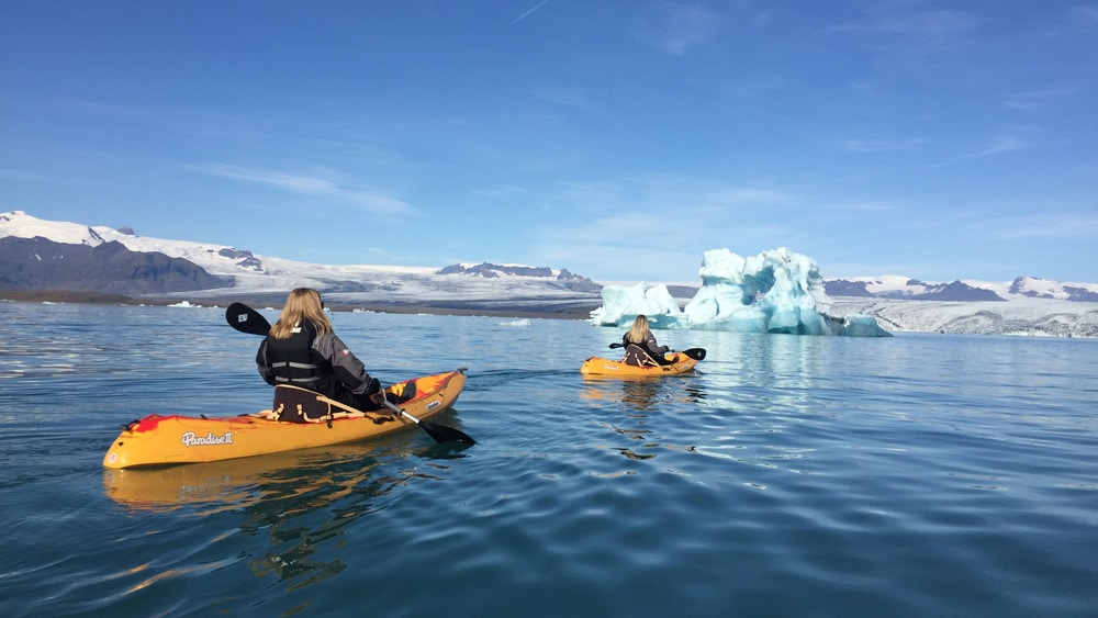 Two girls kayaking in an Ice lagoon