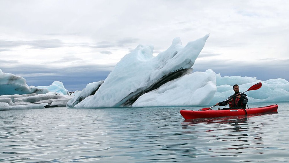 Kayaking around big iceberg